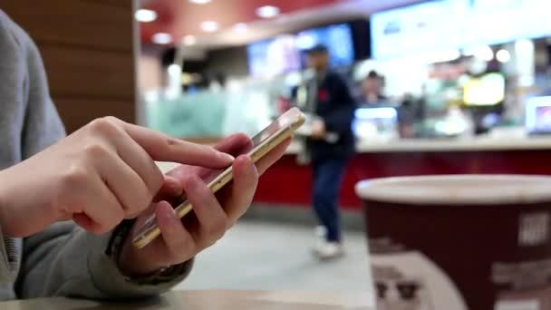 Žena čte zprávy na mobilním telefonu v restauraci rychlého občerstvení mcdonalds