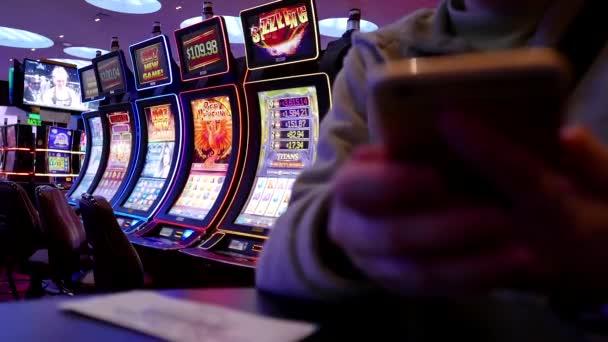 Žena čte mobilní telefon zprávu uvnitř Hard Rock Casino