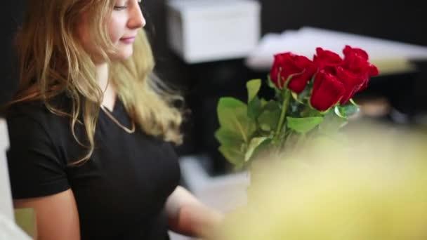 A lány teszi a csomagolás a rózsák a virágbolt.