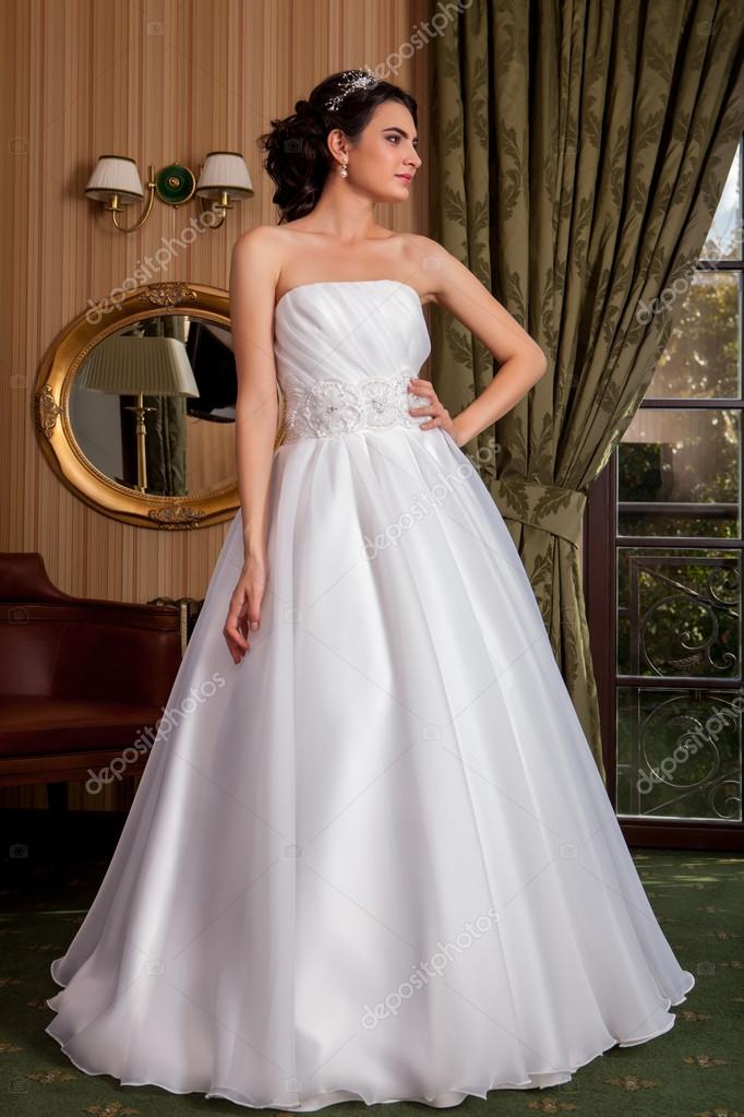 ca1645777 Vestido de novia. Joven esposa intenta encendido un vestido de novia en el  salon — Foto de migfoto