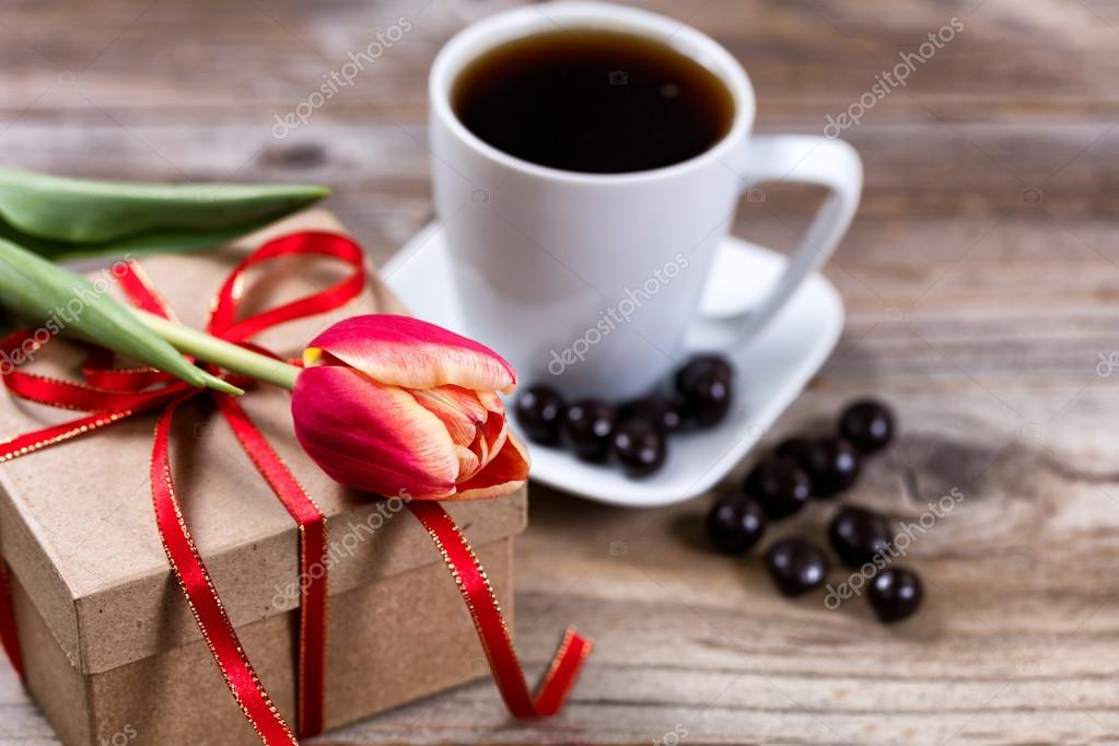 Single cut tulip on gift box with coffee and chocolate on stress