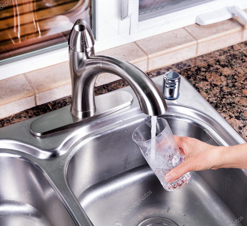 Vaso se llenó con agua del grifo de la cocina el fauce — Foto de ...