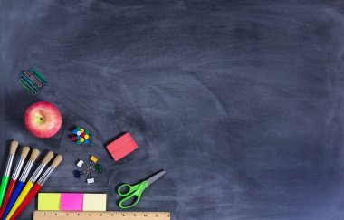 Simple back to school supplies on erased black chalkboard