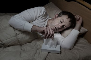 Sick mature man using tissue while in bed