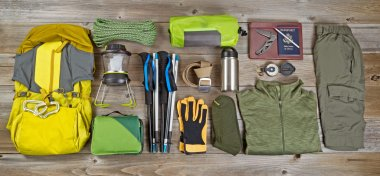 Hiking and camping gear organized on rustic wooden boards
