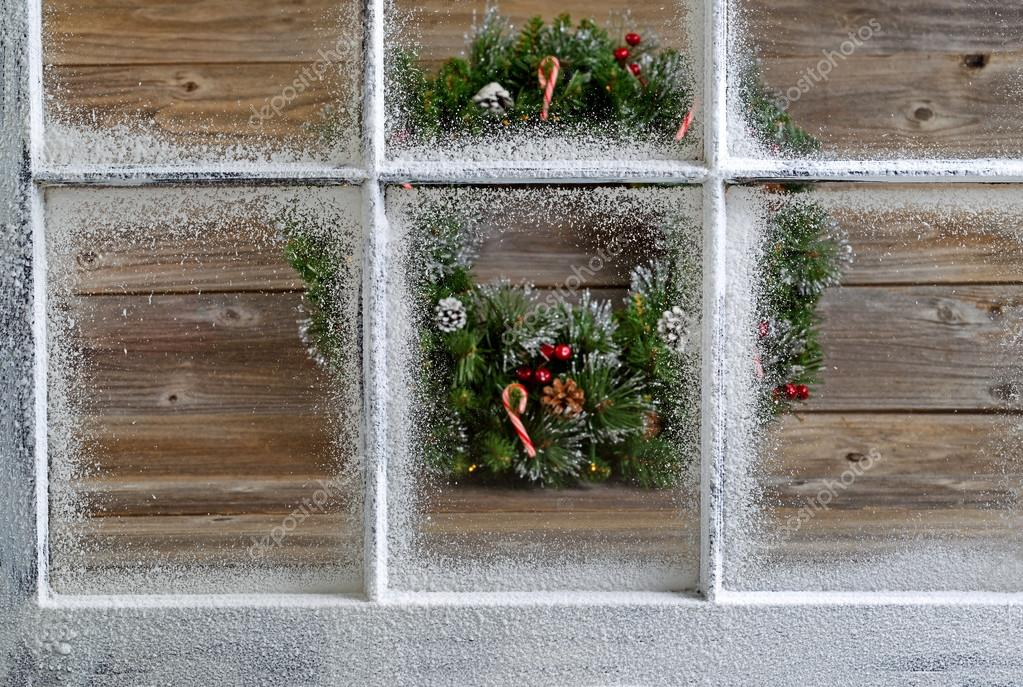 Snow covered window with decorative Christmas wreath on rustic w