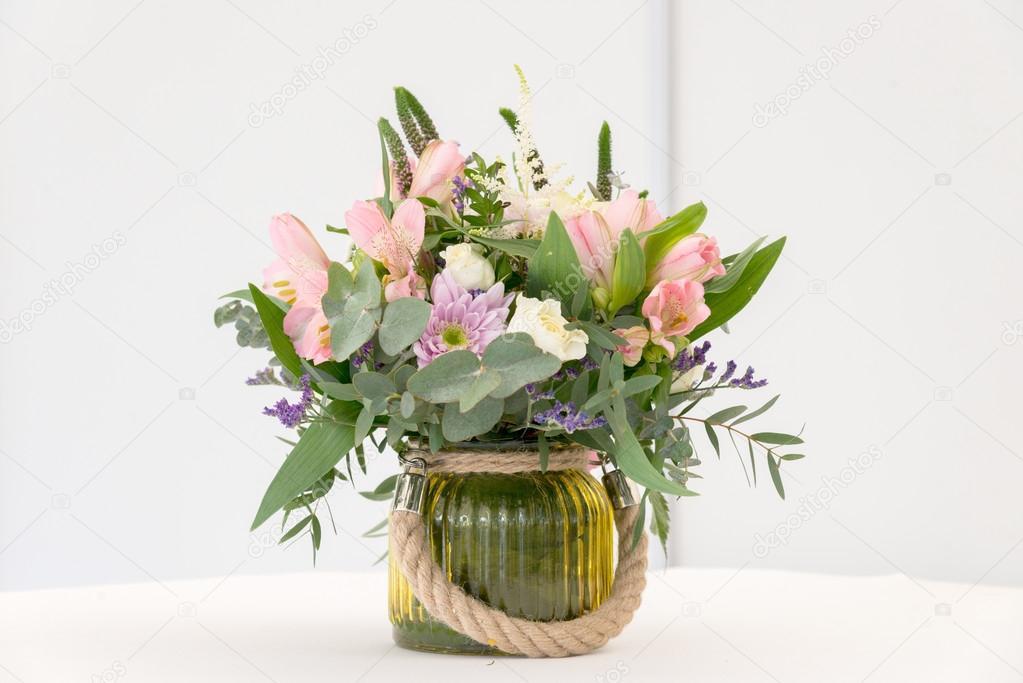 schöne Blumen-Arrangement auf weißen festlich gedeckten Tisch ...