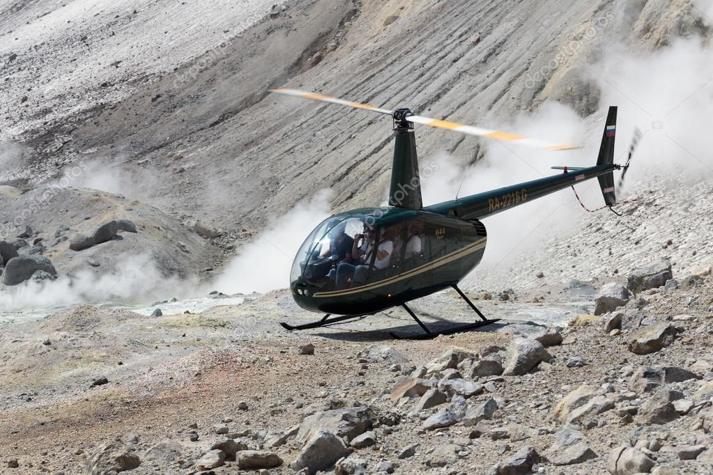 Touristic Helicopter in crater of active volcano on background of smoking fumaroles