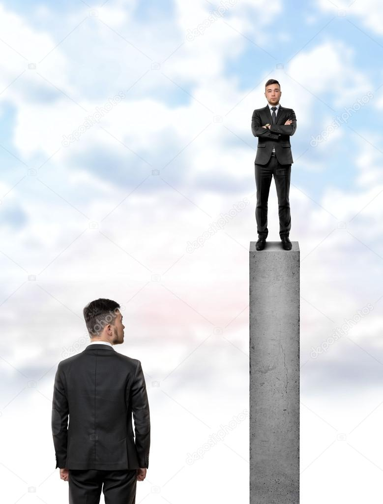 back view businessman looking at other man standing on the top of a