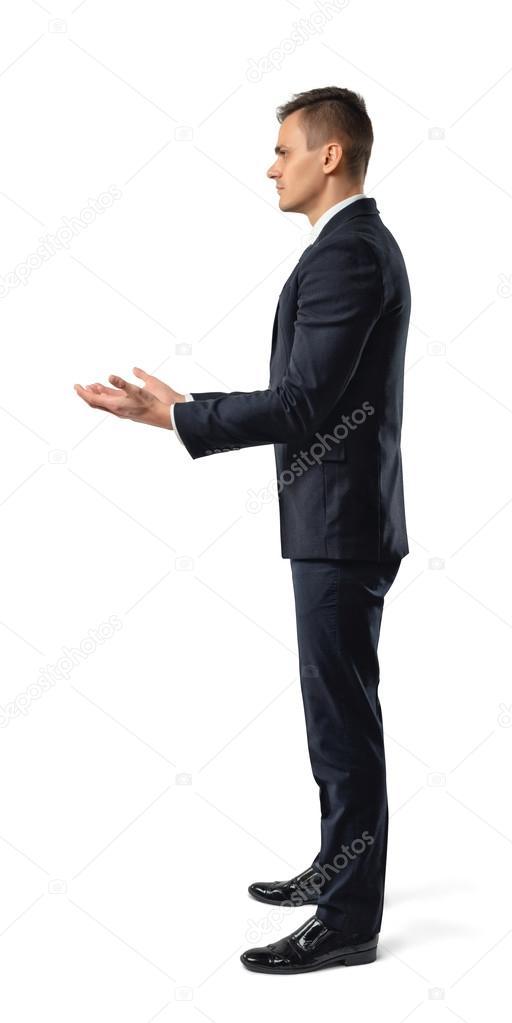 Vue latérale d homme d affaires tenant quelque chose dans ses mains devant  lui e7857742198