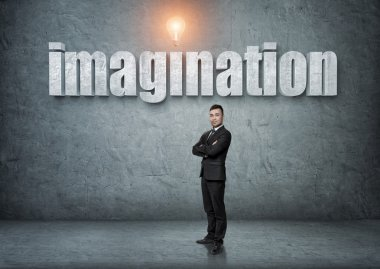 Businessman stands with big 3d imagination word above