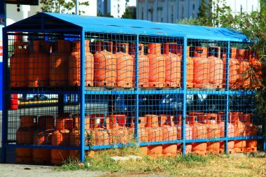 Rows of multiple red gas containers at gas station on the street