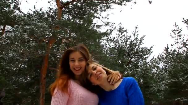 Mutter und Tochter spazieren gemeinsam durch den Park, umarmen, küssen und lachen