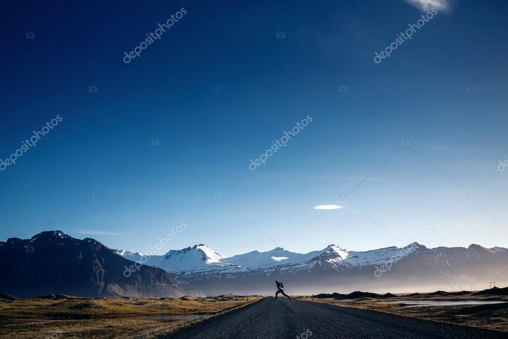 Girl jumping on Winding mountain road