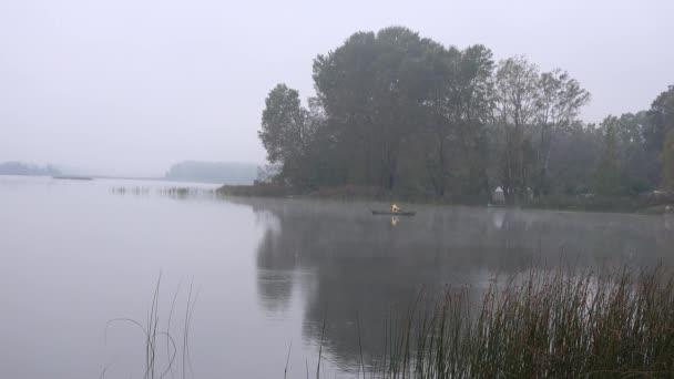 rybář v mlhavé ráno na jezeře na země regionu. 4k