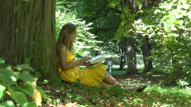 krásná mladá dívka čtení knihy sedí u stromu a lidí, kteří jdou v parku. 4k