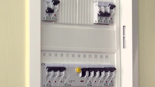 Hand checking and turning on circuit breakers in electrical fuse box ...
