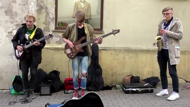 Mladý roztomilý charismatický kluci kluci hrát instrumentální hudbu na ulici.