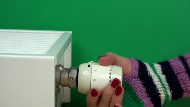 Frauenhand mit Handschuh zur Temperatureinstellung des Heizkörperthermostats auf grün.