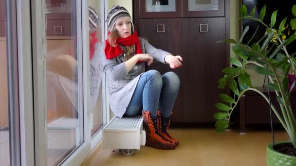 Heiße Frau ausziehen Mütze und Schal auf Kühler sitzt. Temperatur steigt