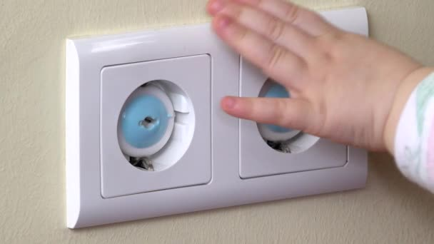 Baby hand reaching for an electrical outlet covered with blue safety plugs