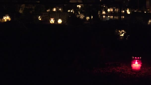graveyard decorated with colorful candles at night. Focus change. 4K