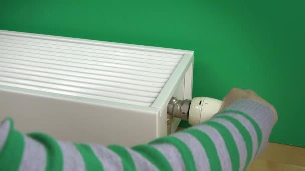 Ženské ruce zvýšit teplotu radiátoru a teplé ruce na to