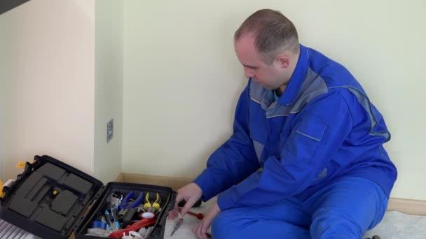 Dělník elektrikář volat mobil a konzultovat s kolegy.