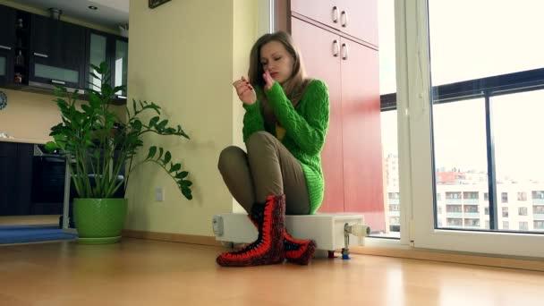 Young zmrazené žena doma nastavení termostatu na radiátor