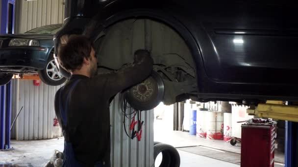 mužské pracovník opravy automobilů brzdový systém v práci.