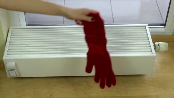Mädchen legt zu Hause rote Wollhandschuhe auf Heizkörper.