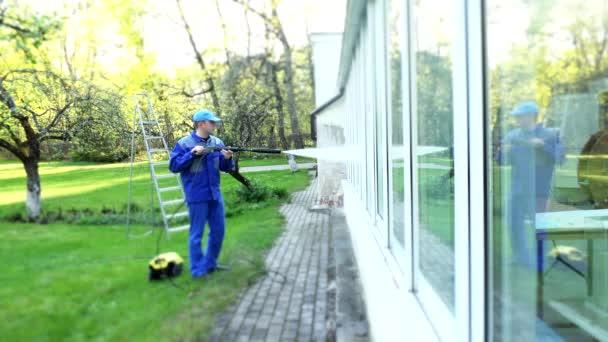 Muž praní konzervatoři okno s pramenem vody odráží na sklo. Zaměření.