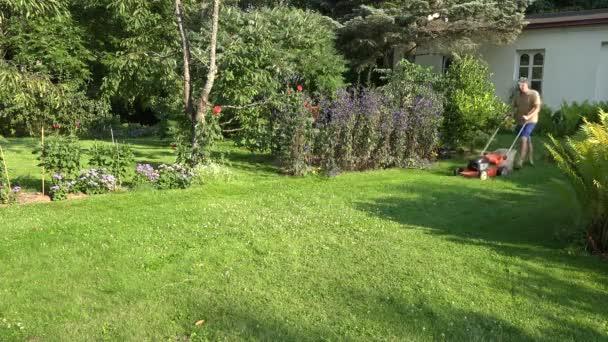 férfi Kertész ember kaszálás a gyep a tanya ház udvarán. 4k
