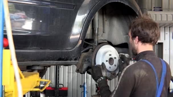 Mechanik přidá nový brzdový kotouč do starého rezavého auta.