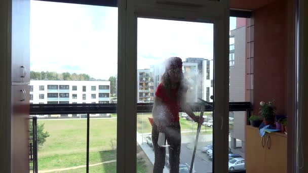 young pretty woman spray chemical and wipe window at clients home.