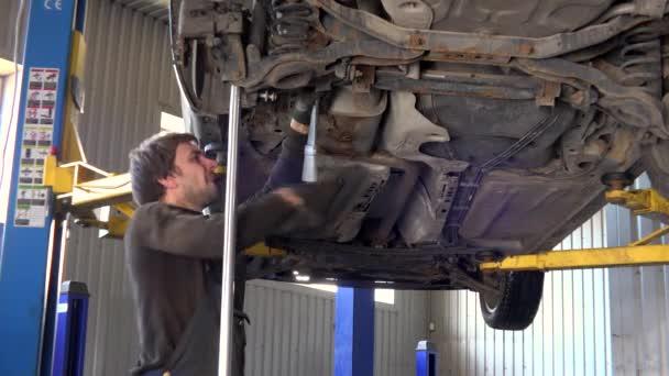 automechanik s klíčem utáhněte auto zdvižené automobilu na servis