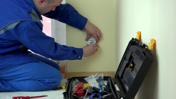 Elettricista operaio riparare una presa elettrica in appartamento