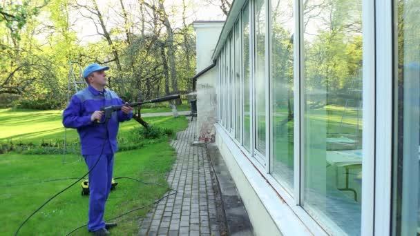 profesionální muž čištění špinavá okna s vysokotlakým vodním paprskem