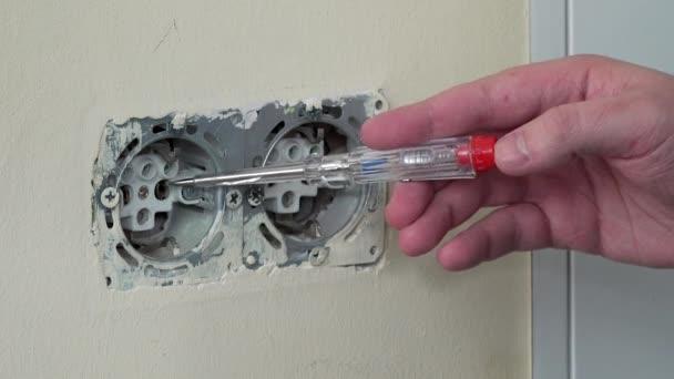 Mano di elettricista verifica tensione elettrica su una presa a spina
