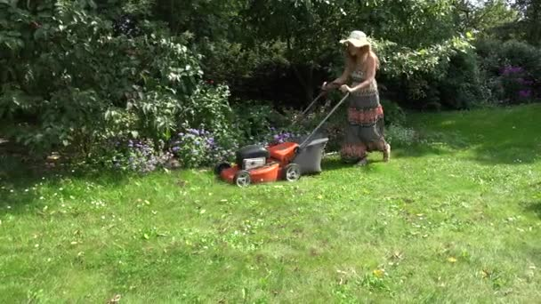Zahradní zaměstnankyně stříhání trávníku poblíž květinové záhony a ovocné stromy. 4k