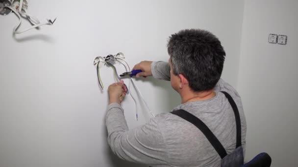 Dělník přestřihuje dráty kleštěmi. Elektrická instalace