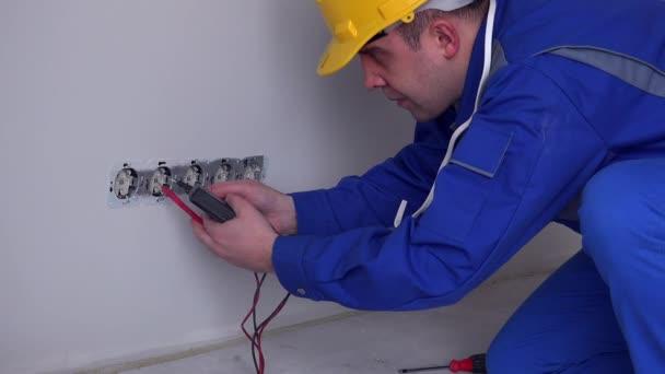 villanyszerelő ellenőrizze a konnektort egy speciális eszközzel az új lakásban. 4K