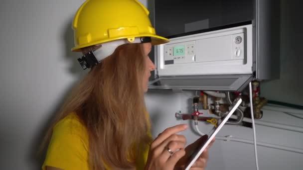 Technikermädchen mit Tablet-Computer inspiziert Gasheizung