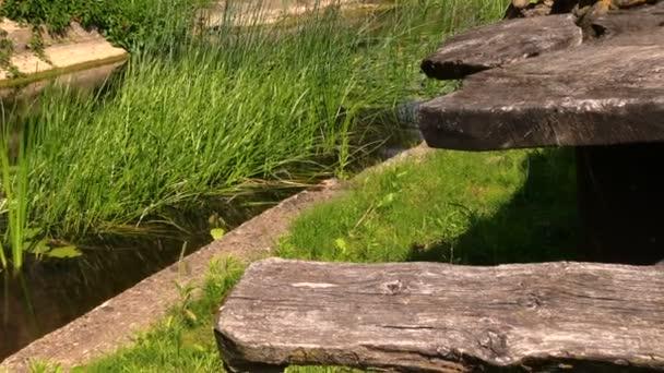 dřevěný stůl a lavice u malé řeky proud