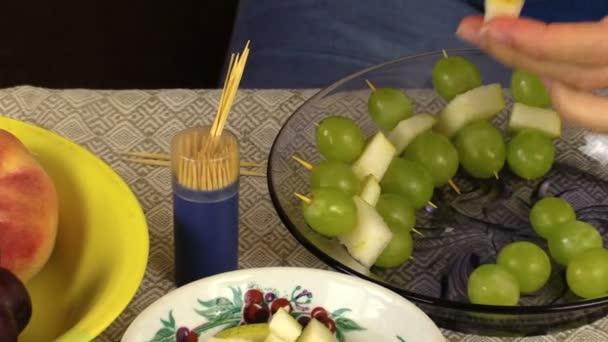 terhes nő előkészíti a szőlő és gyümölcs darabokat desszert