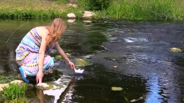 lány fut papír csónak alatt gyorsan áramló patak nyáron zöld park