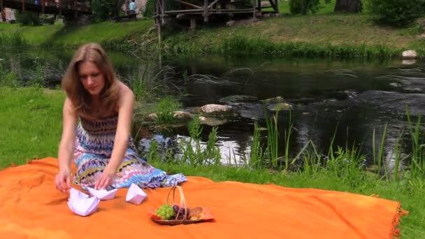 těhotná žena poblíž říční vody a skládání papíru lodí