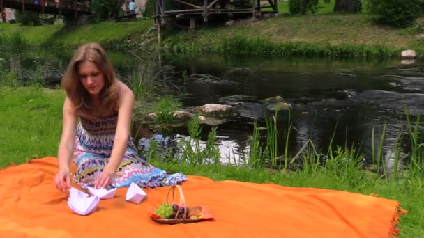 Pregnant woman near river water and fold paper ships