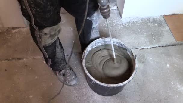 Operaio mescolare il cemento colla per piastrelle sul secchio con strumento video stock - Colla per piastrelle su piastrelle ...
