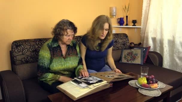 Young pregnant woman looking at photo album with senior grandma